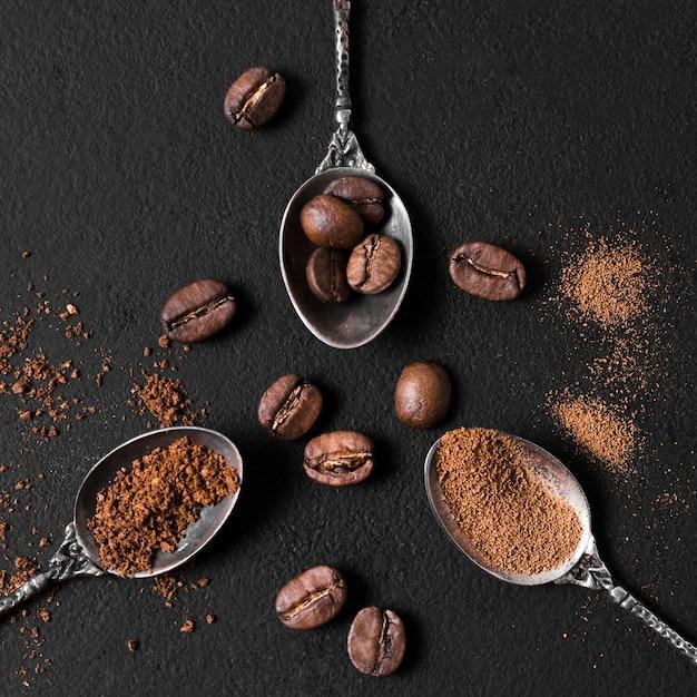 Disposición de la vista superior de cucharas llenas de granos de café tostados y polvo Foto Premium