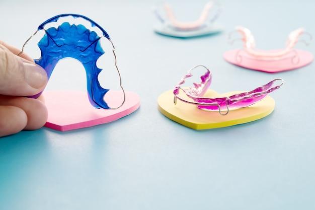 Dispositivo ortodóntico del criado dental en el fondo azul. Foto Premium