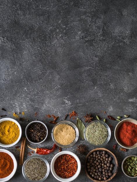 Las diversas especias secas planas ponen en pequeños cuencos en fondo gris. vista superior, copia espacio Foto Premium