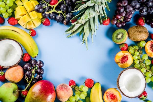 Diversas frutas tropicales concepto de vitaminas de verano coco uva piña melocotón nectarina fresa manzanas mango plátano. espacio de copia de la vista superior Foto Premium
