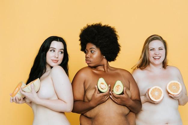 Diversas mujeres desnudas con curvas sosteniendo frutas sobre sus pechos Foto Premium