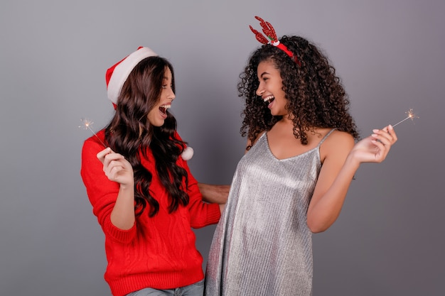 Diversas mujeres felices con brillantes bengalas con sombrero de navidad aislado en gris Foto Premium