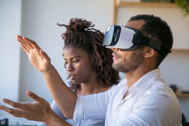 Diversos colegas que prueban el simulador de realidad virtual juntos Foto gratis