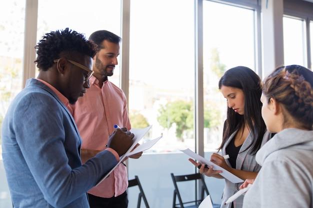 Diversos colegas tomando notas mientras comparten ideas Foto gratis