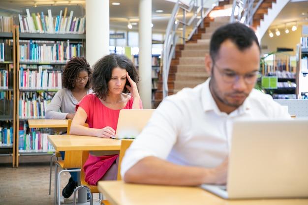 Diversos estudiantes adultos que trabajan en la computadora en el aula Foto gratis