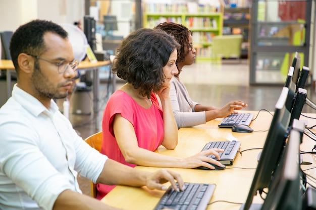 Diversos estudiantes adultos trabajando en clase de informática Foto gratis