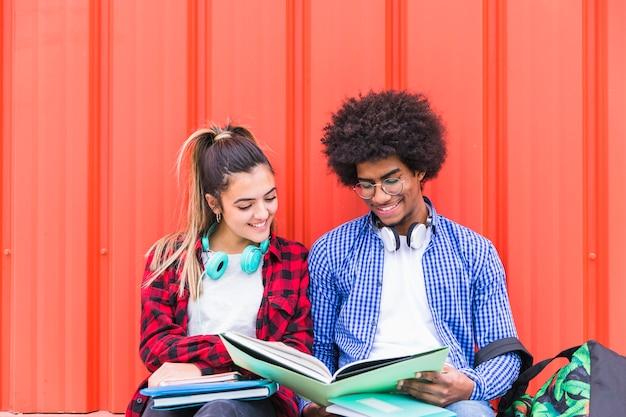 Diversos estudiantes estudiando juntos sobre un fondo naranja. Foto gratis