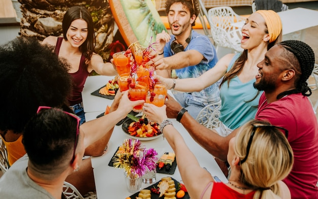 Diversos jóvenes divirtiéndose celebrando cócteles Foto Premium