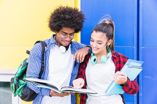 Diversos pares adolescentes que se oponen a la pared azul y amarilla que estudian juntos Foto gratis