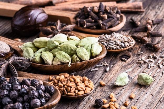 Diversos tipos de especias indias enteras en primer de madera del fondo. Foto Premium