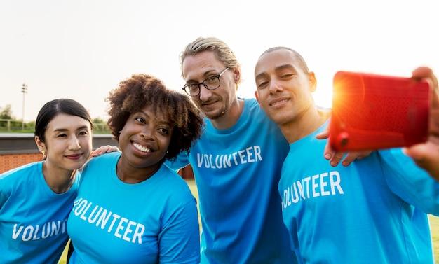 Diversos voluntarios tomando una selfie juntos Foto gratis