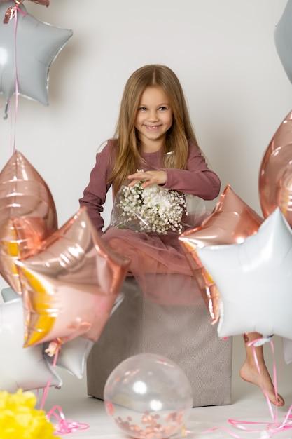 Divertida chica rubia entre globos y sosteniendo un ramo de flores silvestres Foto Premium