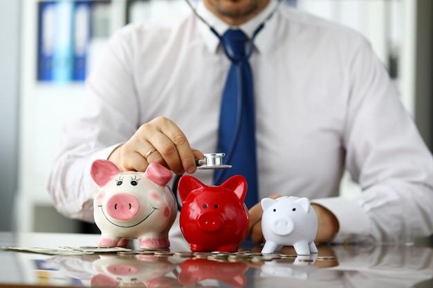Divertido empresario escucha tres piggybanks por dinero en efectivo Foto Premium