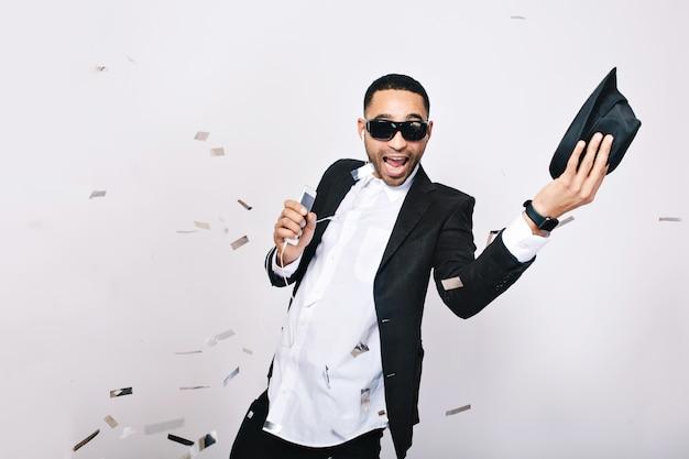 Divertido joven emocionado en traje con gran celebración de fiesta en oropel. usar gafas de sol negras, sonreír, cantar, escuchar música, expresar positividad. Foto gratis