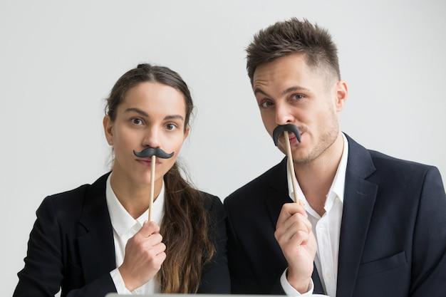 Divertidos colegas haciendo caras tontas sosteniendo bigote falso, retrato en la cabeza Foto gratis