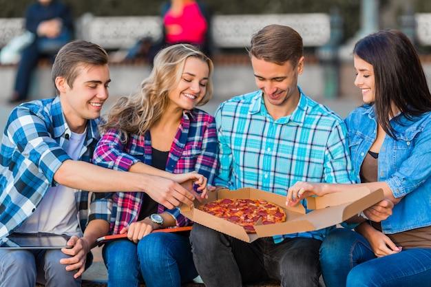 Divertidos jóvenes estudiantes, están comiendo pizza. Foto Premium