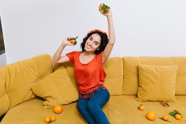 Divirtiéndose en casa de una mujer joven y bonita emocionada increíble con cabello rizado de corte morena sonriendo en el sofá naranja entre mandarinas en la sala de estar. Foto gratis