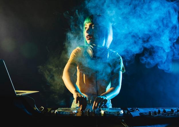 Dj femenino en club cubierto por humo colorido Foto gratis