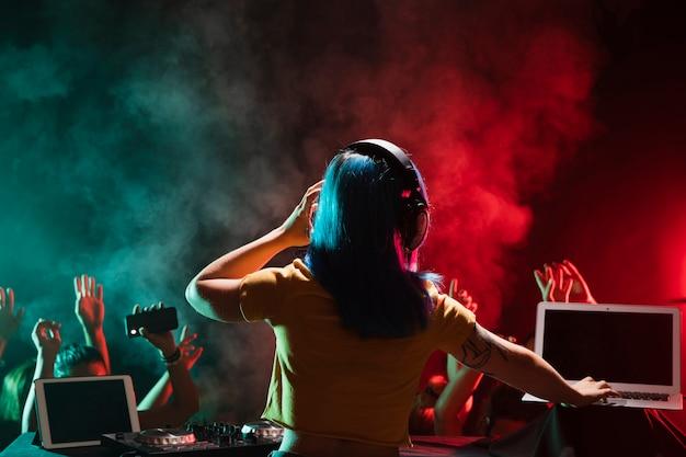 Dj femenino en la mesa de mezclas en el club Foto gratis