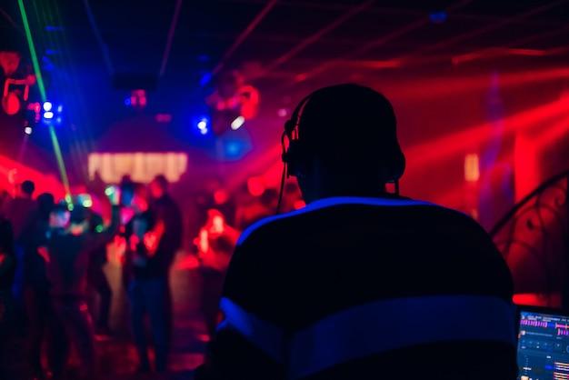 Dj mezcla música en una discoteca con gente bailando Foto Premium