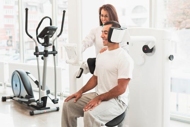 Doctor ajustando dispositivo médico para paciente masculino Foto gratis