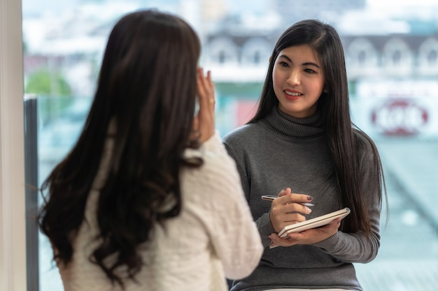 Doctor asiático del psicólogo profesional de la mujer que da la consulta al paciente femenino Foto Premium