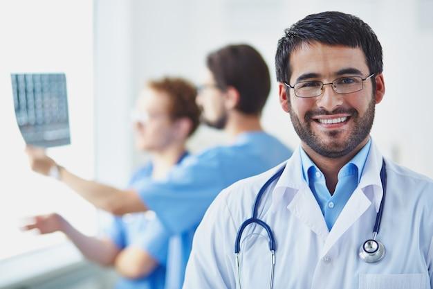 Doctor con compañeros de trabajo analizando una radiografía Foto gratis