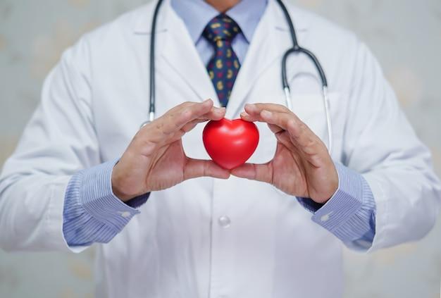 Doctor con corazón rojo en la mano en el hospital. Foto Premium