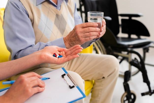 Doctor dando a un anciano sus pastillas Foto gratis