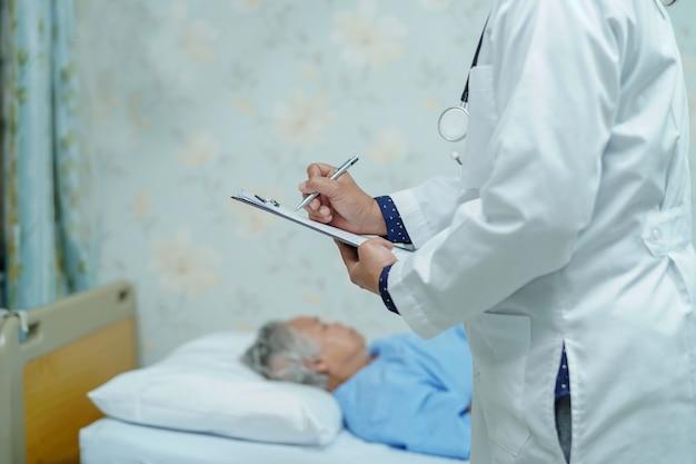 Doctor escribiendo el diagnóstico en el portapapeles en el hospital. Foto Premium