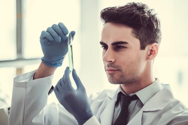 Doctor en guantes está trabajando con tubos de ensayo en el laboratorio. Foto Premium