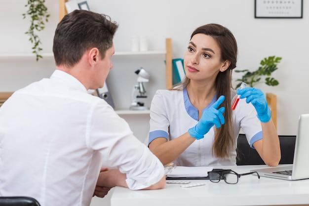 Doctor hermoso que muestra una muestra de sangre al paciente Foto gratis