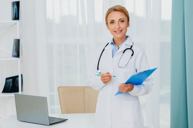 Doctor holding portapapeles mirando a cámara Foto gratis