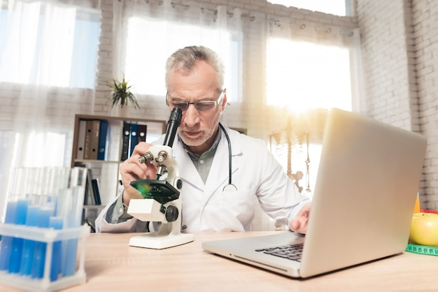 Doctor hombre mirando a través de un microscopio en un laboratorio. Foto Premium
