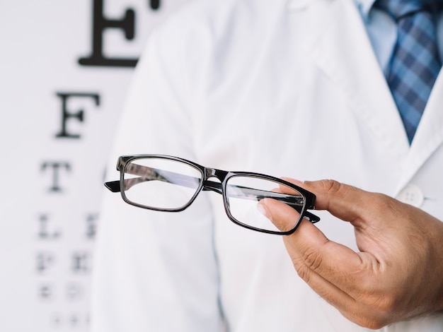 Doctor hombre sosteniendo un par de anteojos en sus manos Foto gratis