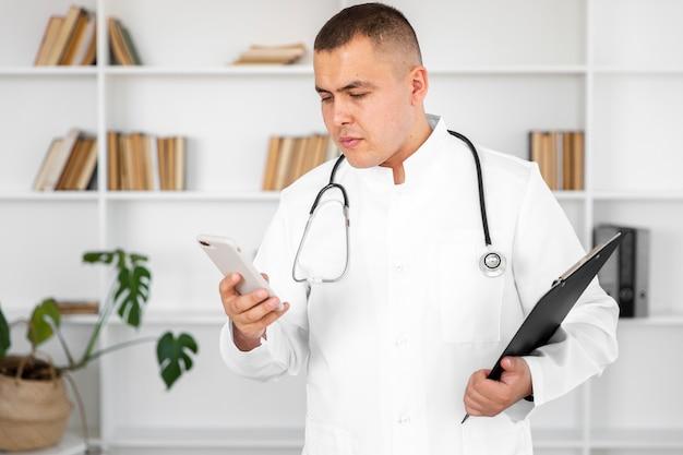 Doctor hombre sosteniendo un teléfono y un portapapeles Foto gratis
