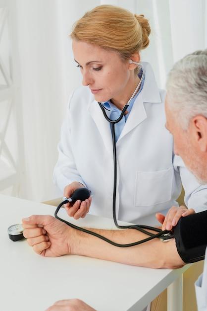Doctor inflando el manguito de presión arterial Foto gratis