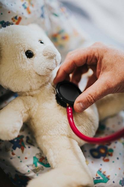 Doctor juguetonamente comprobando el latido del corazón de un oso de peluche Foto gratis