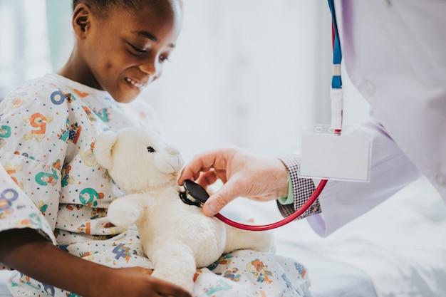Doctor juguetonamente comprobando el latido del corazón de un oso de peluche Foto Premium