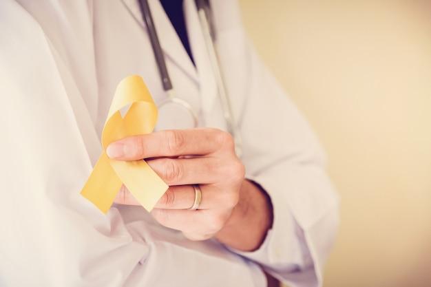 Doctor manos sosteniendo cinta de oro amarillo, conciencia de sarcoma Foto Premium