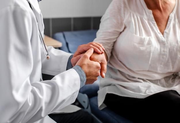 Doctor manos sosteniendo paciente femenino Foto gratis