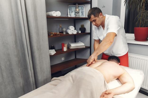 El doctor masajea al hombre en el hospital. Foto gratis