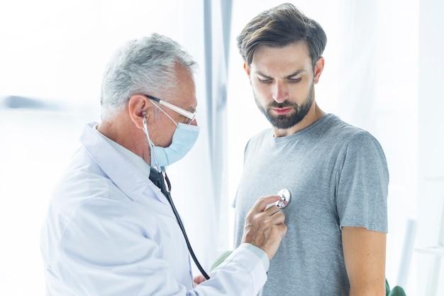 Doctor en máscara examinando hombre barbudo Foto gratis