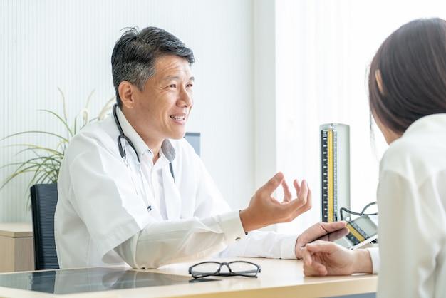 El doctor y el paciente mayores asiáticos están discutiendo Foto Premium