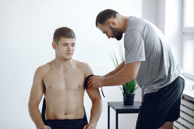 El doctor pega un tipi a un atleta en el hospital Foto gratis