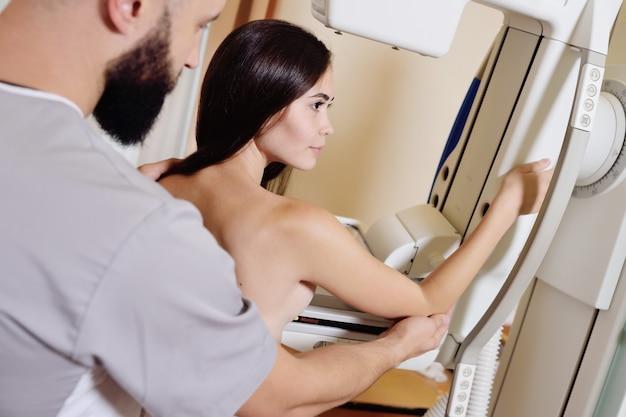 Doctor de pie asistiendo a un paciente sometido a una mamografía de rayos x Foto Premium