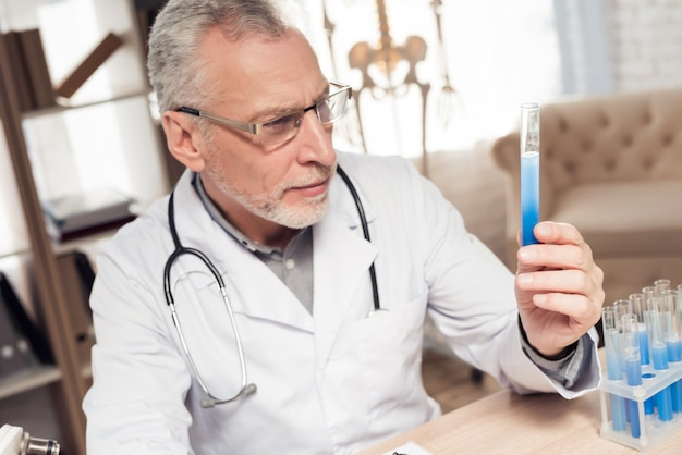 Doctor que se sienta en el escritorio con el microscopio y el estetoscopio. Foto Premium