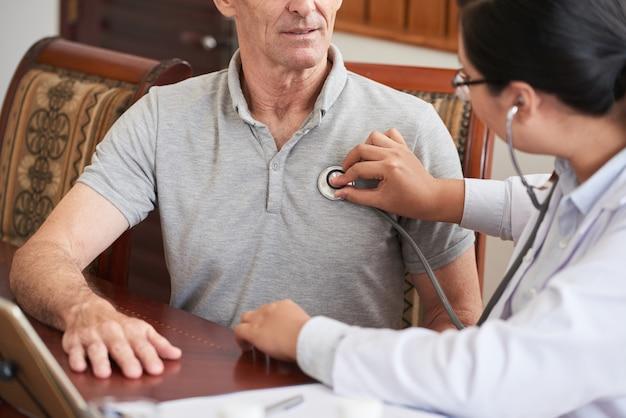 Doctor recortado que controla los latidos del corazón del paciente mayor Foto gratis