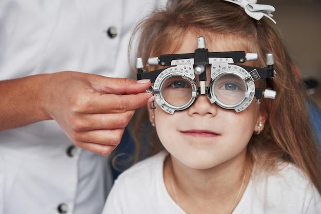 Doctor revisando la vista de la niña y afinando el foróptero Foto Premium
