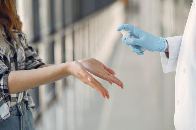 El doctor rocía el antiséptico en las manos del paciente. Foto gratis